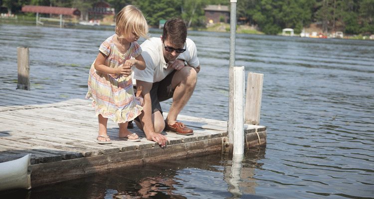 Photo of an adult and a child looking down at a lake