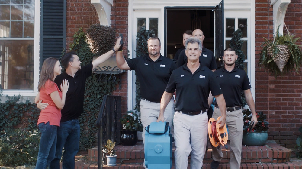 Photo of Steve's Pest Control leaving a home, with satisfied customers on the left